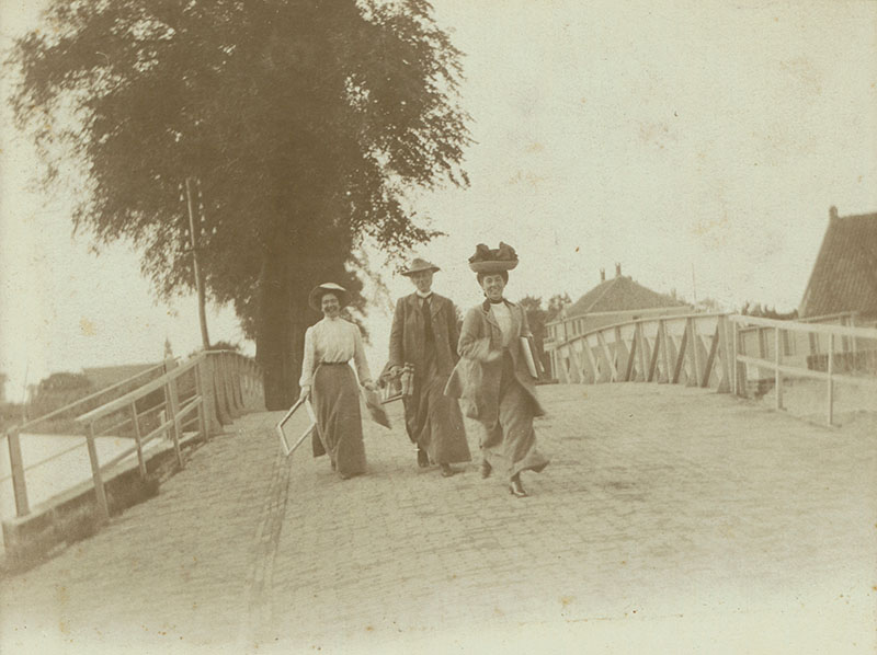 Three woman crossing a bridge. One of the women is running towards the camera, smiling. Behind them is a large tree and buildings