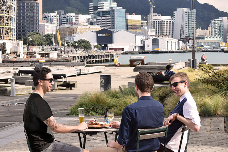 Three men drinking and eating at the Red Gates bar - the waterfront in the background
