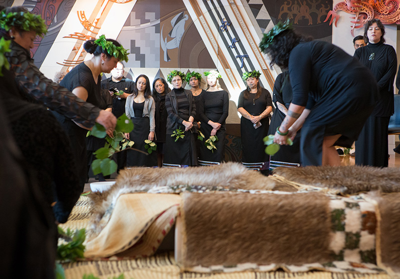 Ladies placing feathered cloaks over the boxes containing Māori remains