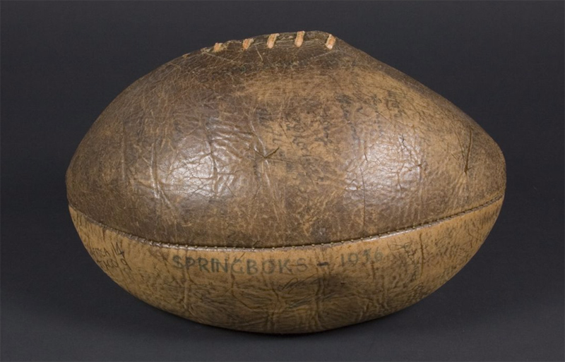 brown leather rugby ball with ink signatures on it