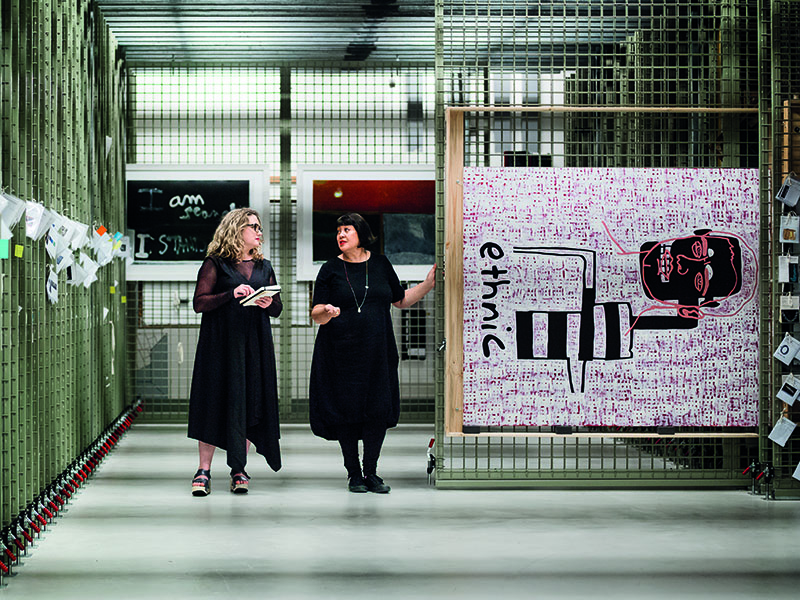 Sarah Farrar and Megan Tamati-Quennell in the paintings storeroom, with a painting on a rail pulled out and on display, with two other paintings in the background