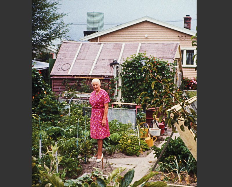 Photograph of a woman standing in her vegetable garden by FR Lamb