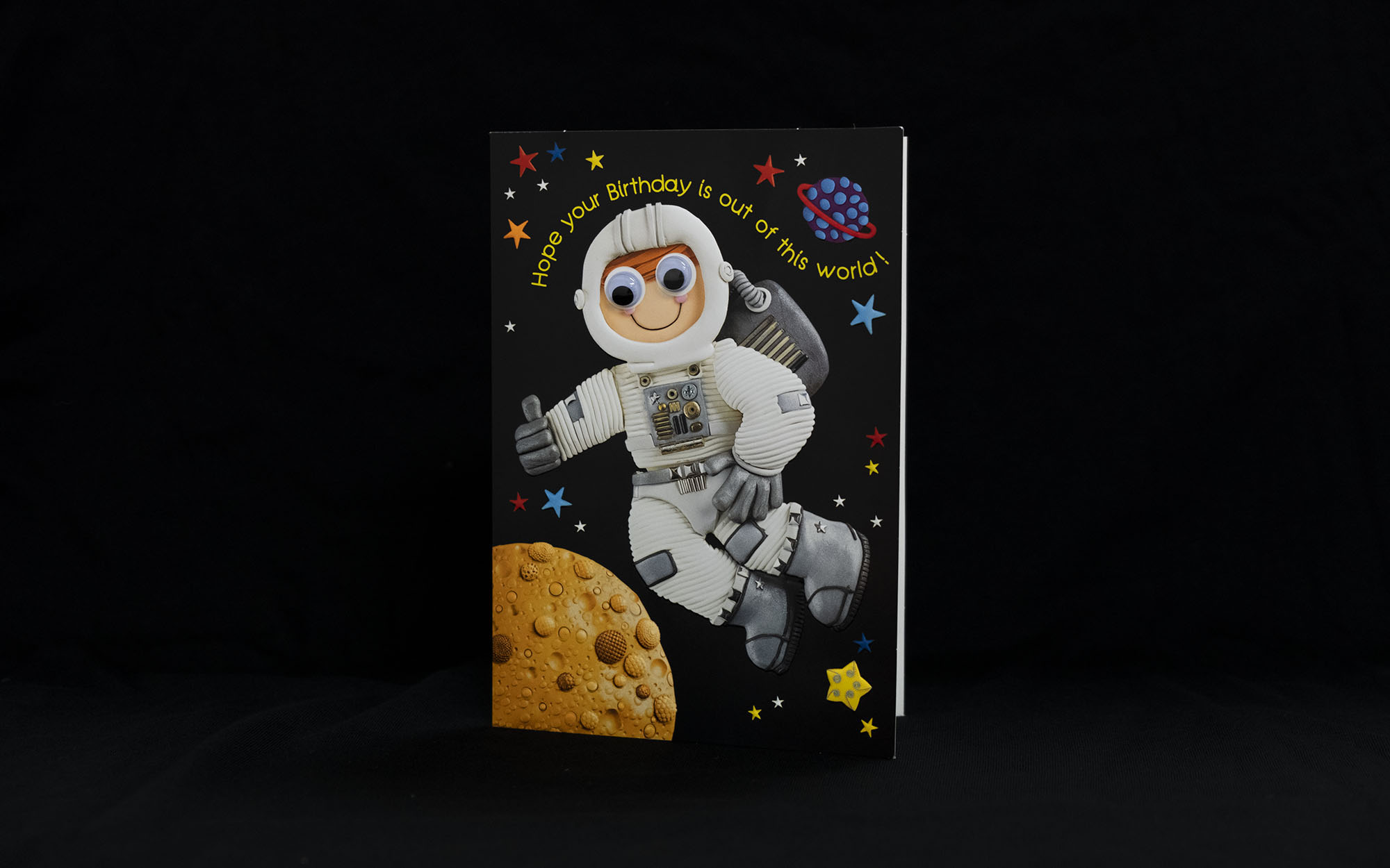 "Birthday card with an astronaut on it and planets and stars. The card says ""Hope your birthday is out of this world!"""