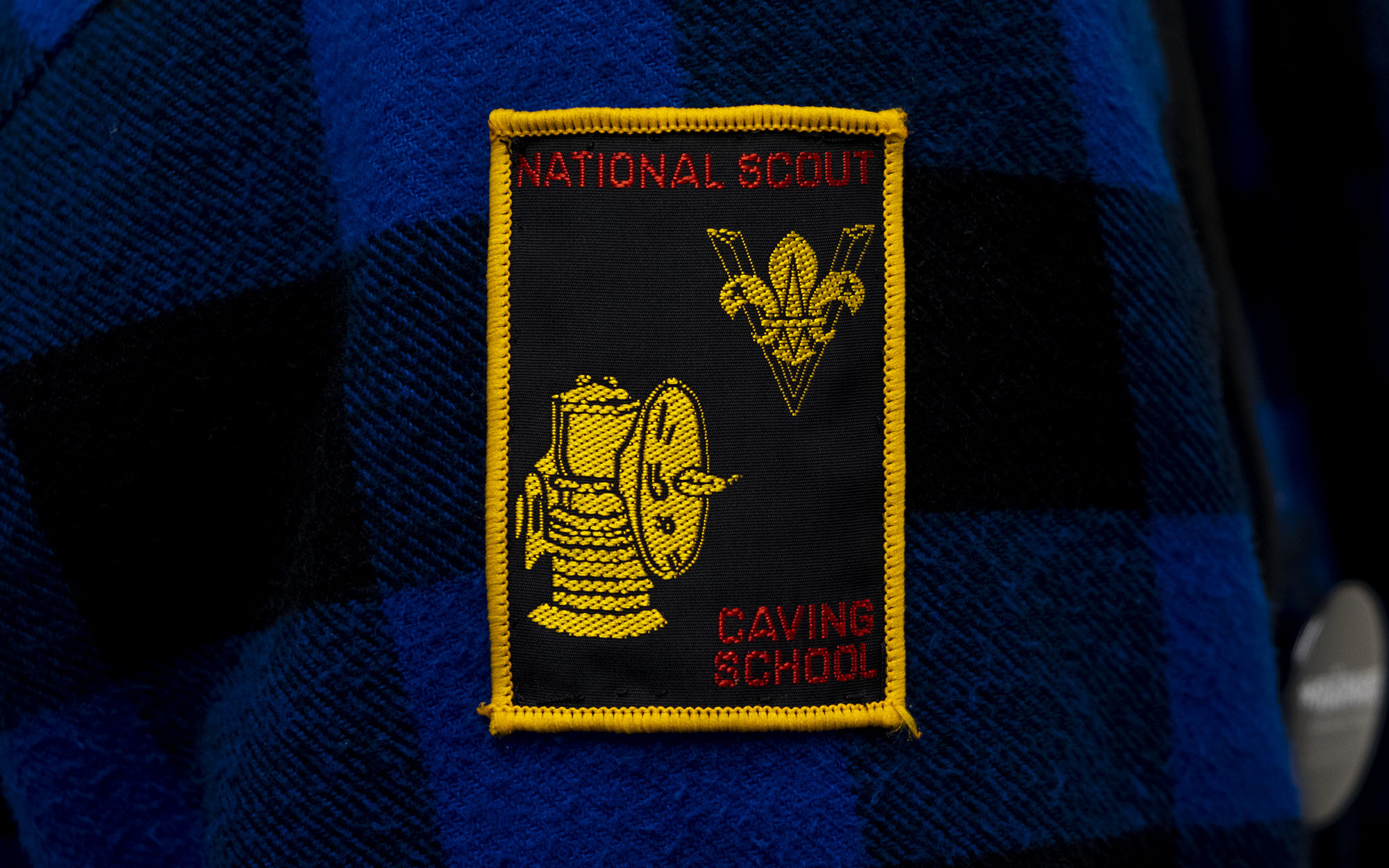 "A badge sewn onto a black and blue checked woollen jacket. The badge has a bright yellow border and says ""National scout, caving school"" on it with a picture of a lantern and the Scouts logo"