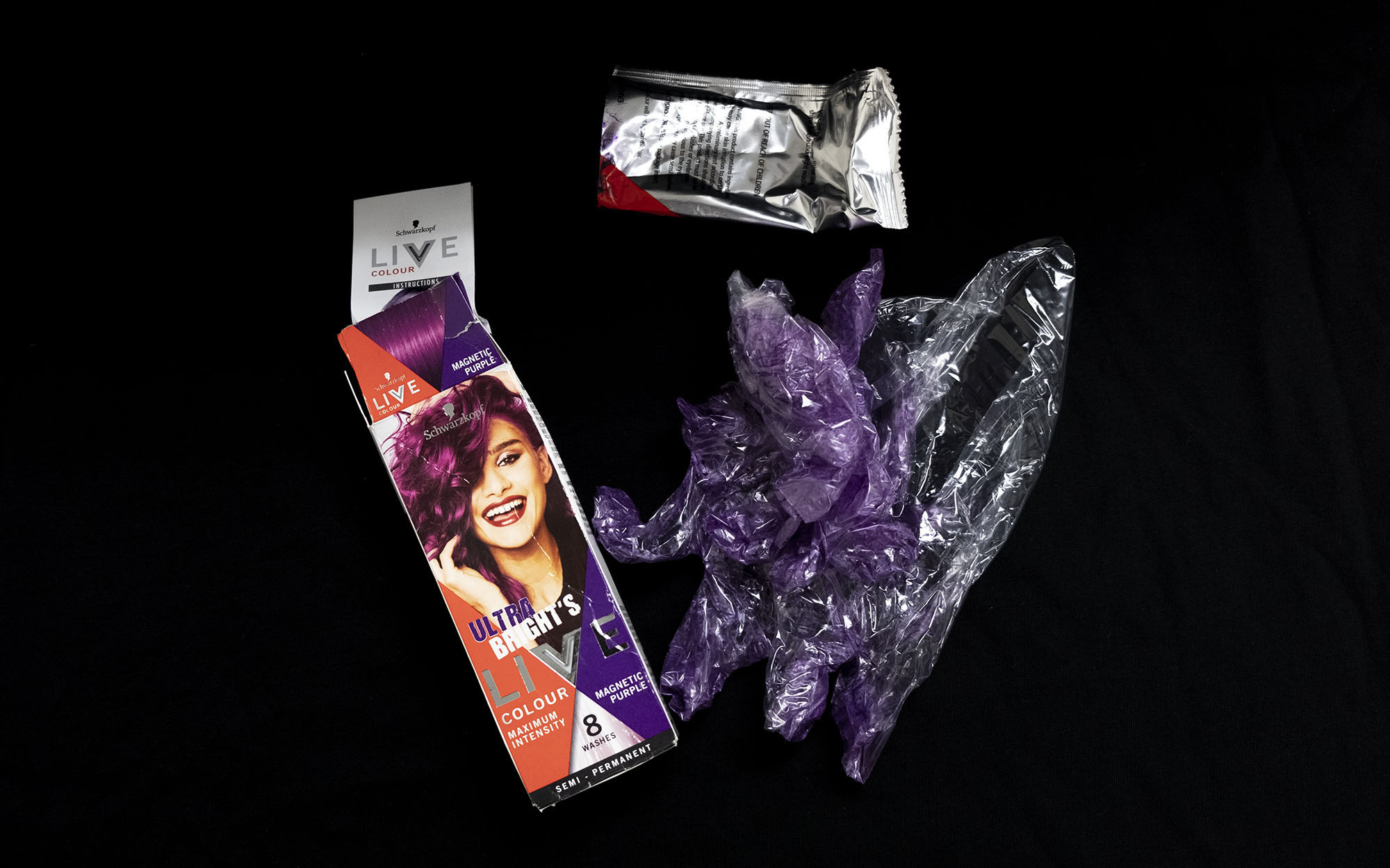 The contents of a used box of hair dye, including gloves dyed purple from application