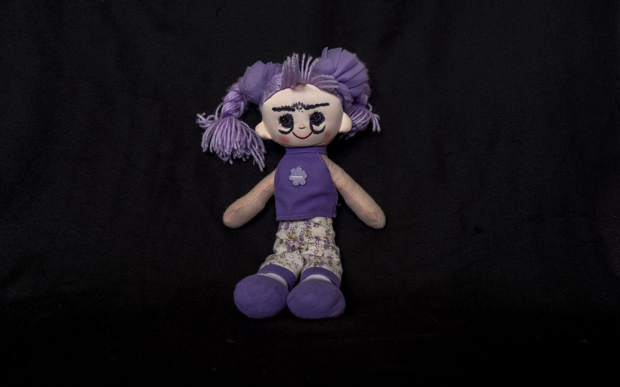 Smiling plush doll with purple hair, a purple singlet, purple shoes, and cream pants with purple flowers and hem