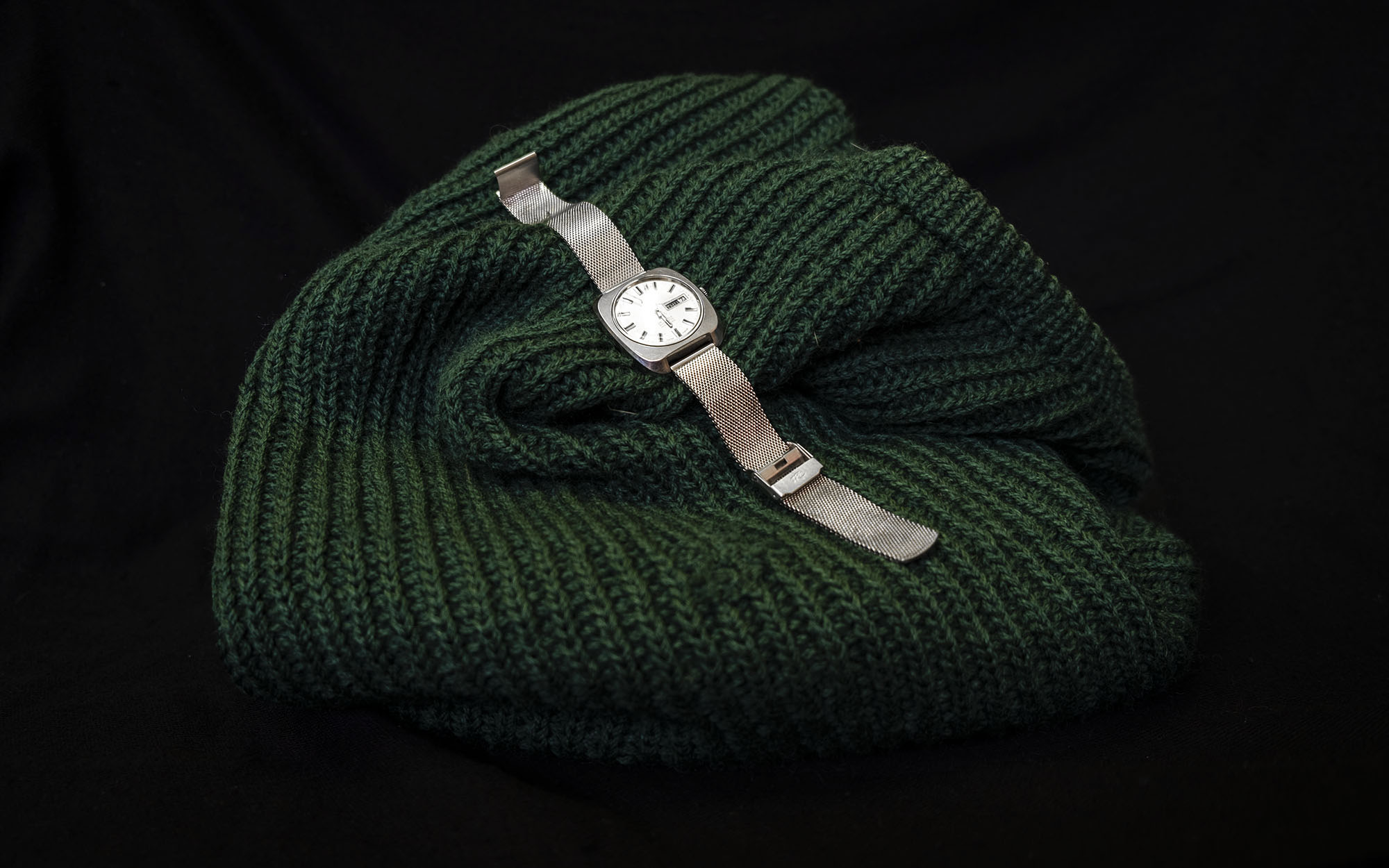 Green knitted jumper and a silver watch