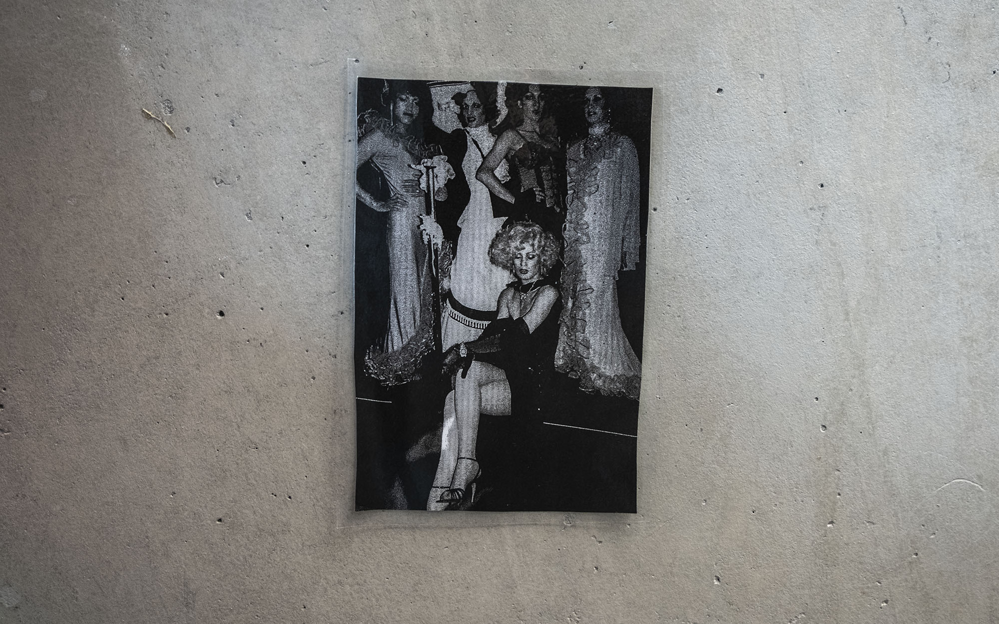 Photo hanging on a concrete wall featuring five people in evening dress
