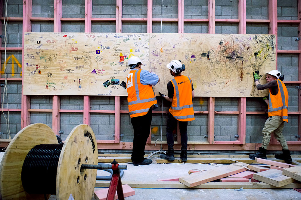 Construction workers hoist a wood panel onto the wall