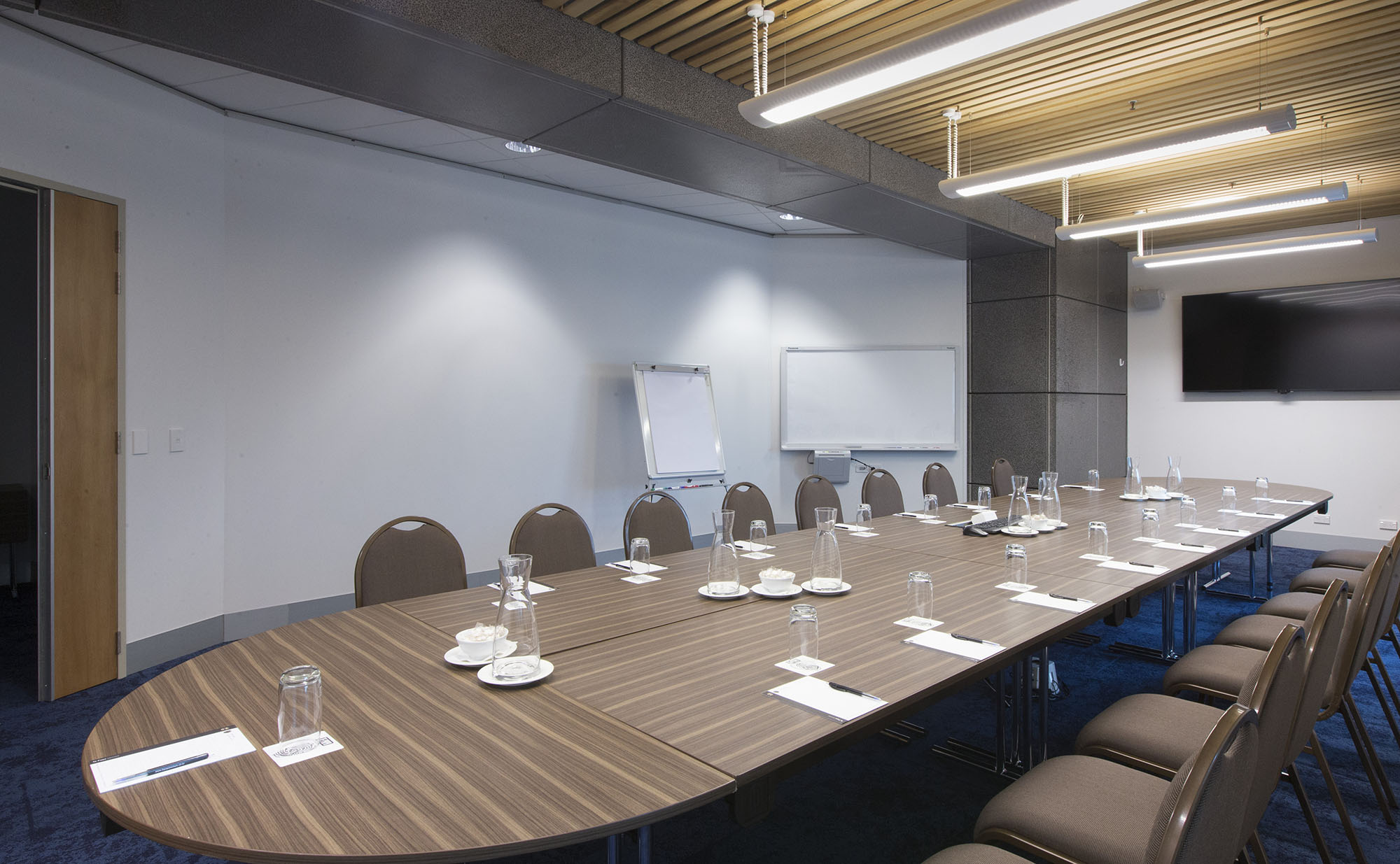 Meeting room showing a very large desk with pens and pads at each seat, and water bottle and mints in the middle. A white board and large pad are near the wall, with a TV screen on the wall