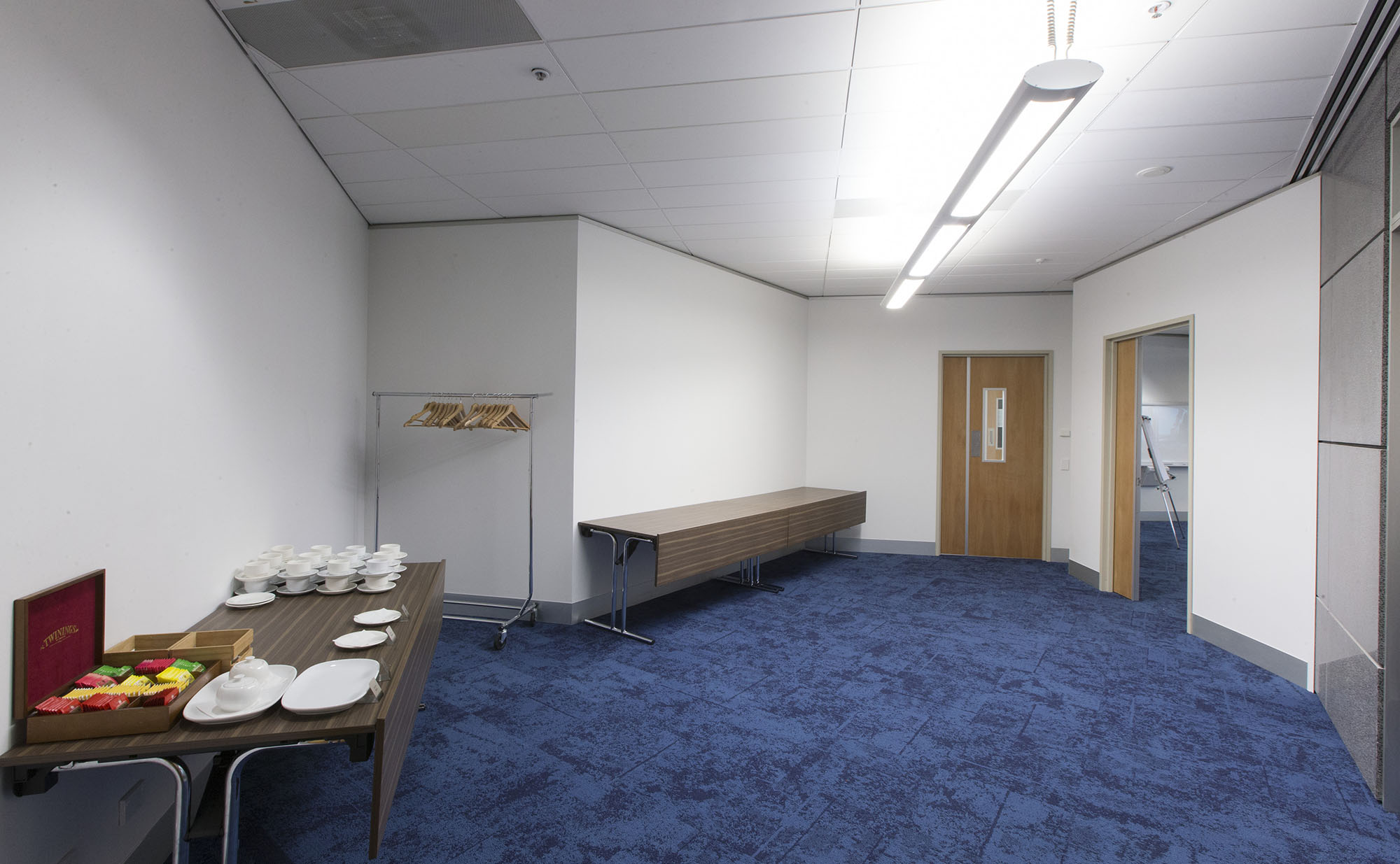 Large space with blue carpet featuring two tables against the wall – one containing tea cups and teabags
