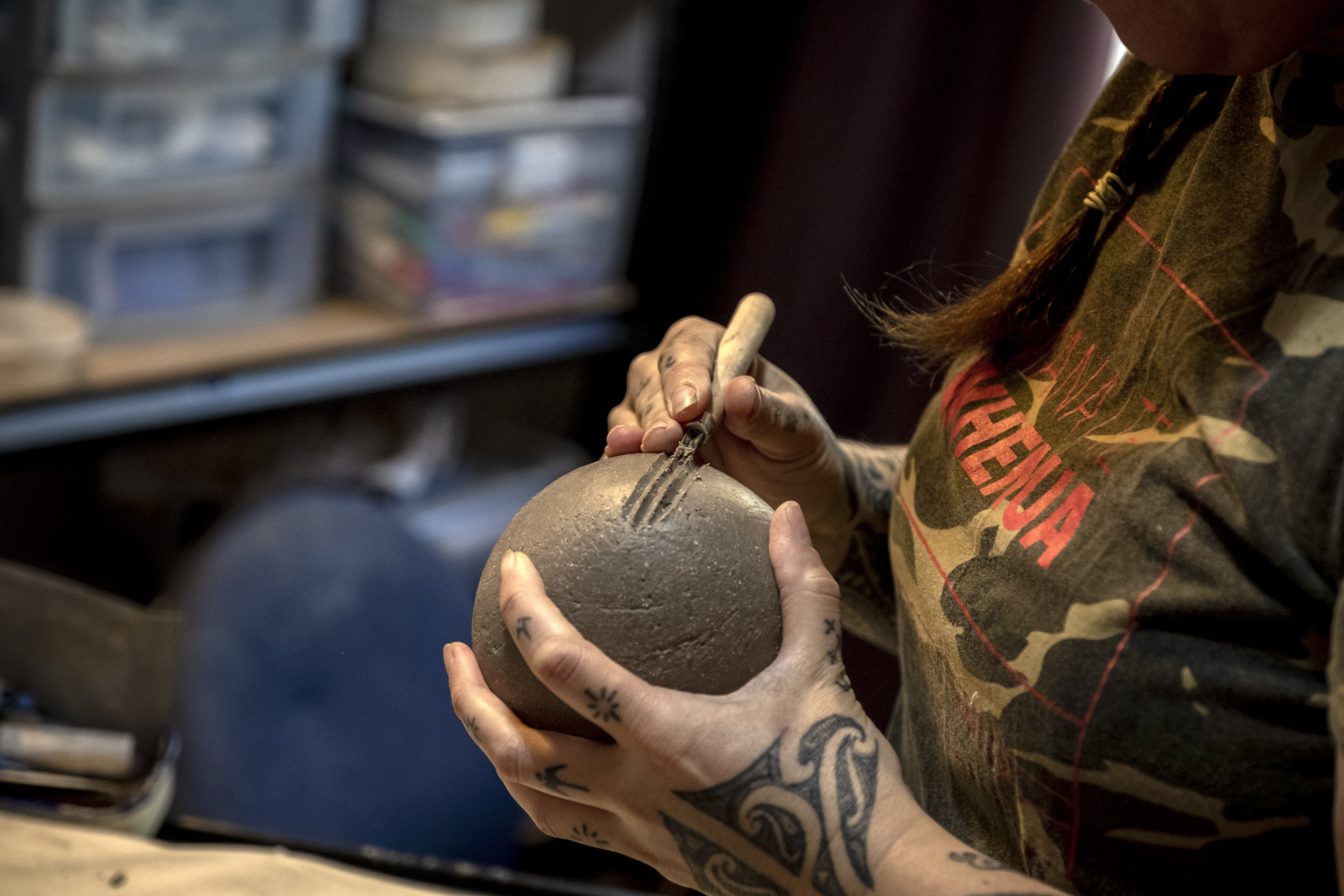 Two hands working on a piece of unfired clay pottery.