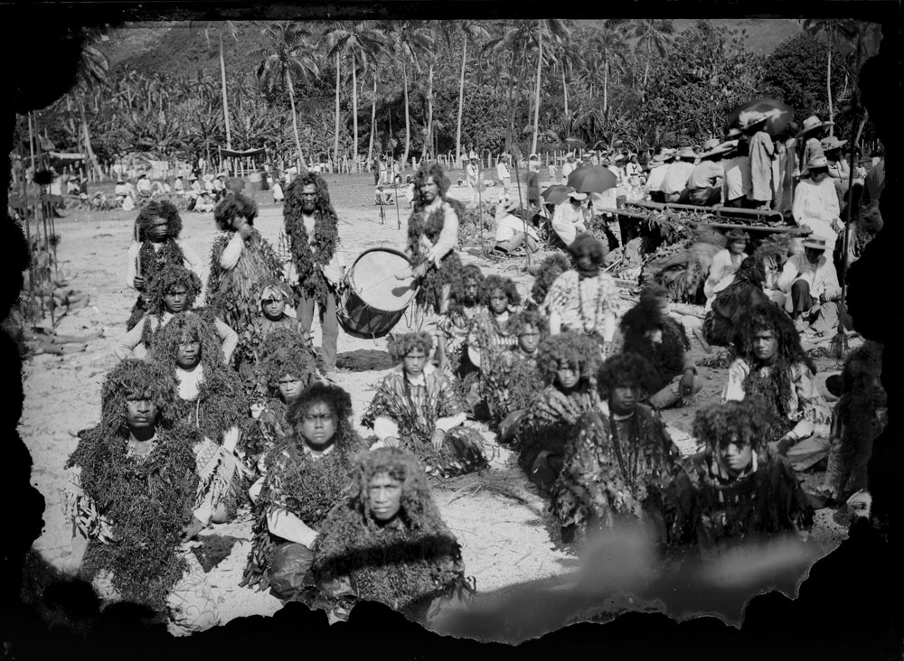 Group of performers dressed in elaborate costumes with a man standing behind them beating a drum. In the background are rows of coconut palms