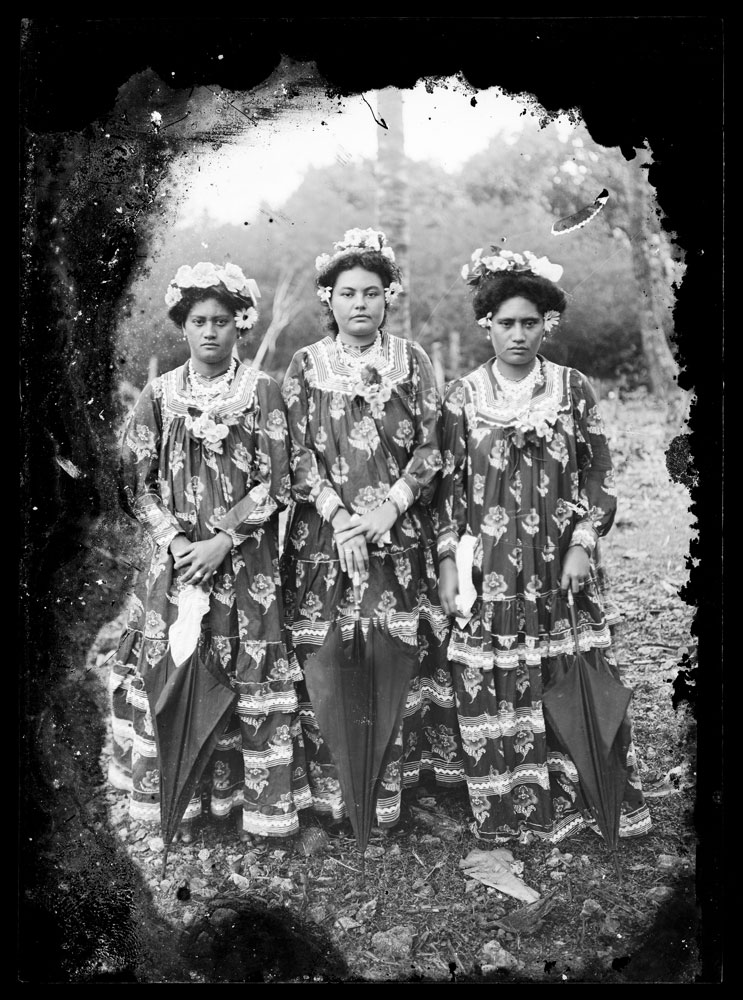 Three ladies in matching outfits holding umbrellas