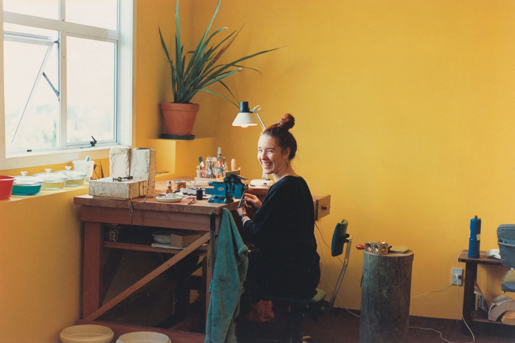 Lisa sits at desk in room with bright yellow walls crafting jewellery