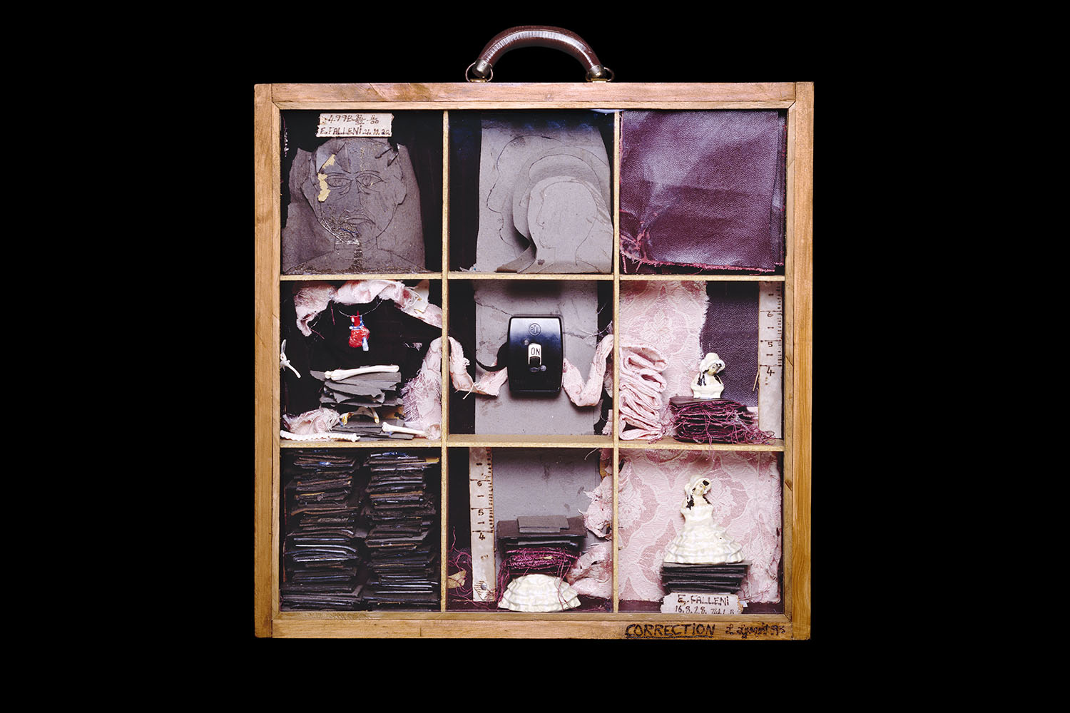 A frame resembling a suitcase divided into nine sections, containing a portrait, fabric swatches, a light switch, and various trinkets