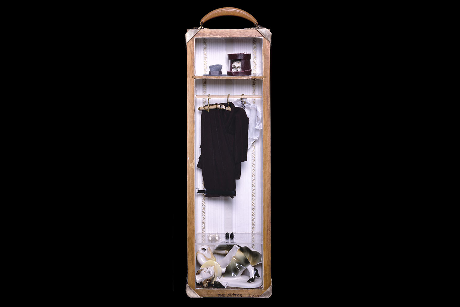 Narrow open half of a suitcase that resembles a wardrobe, inside containing a broken statue of a woman, clothes hanging, and a skull in a hat box
