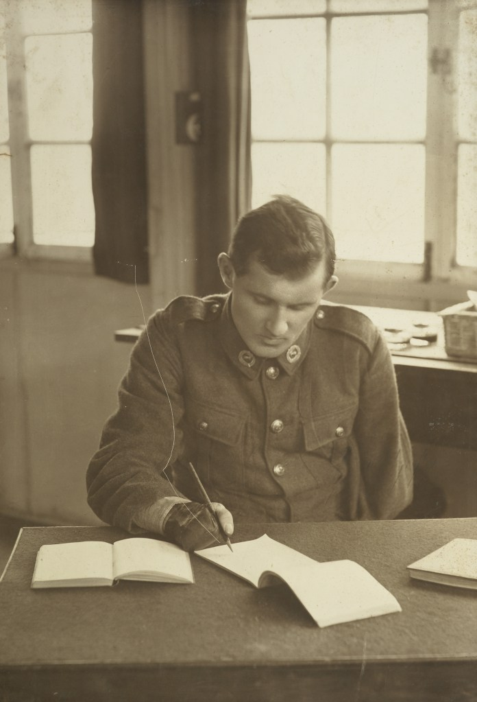 A soldier with one arm sits at a desk