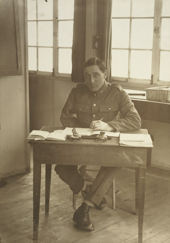 Portrait of an unidentified WWI soldier, right arm amputated, seated at a desk