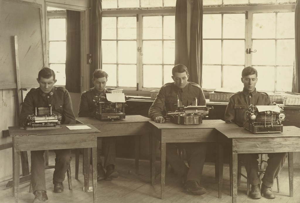 Three soldiers missing an arm each sit in a classroom in front of typewriters