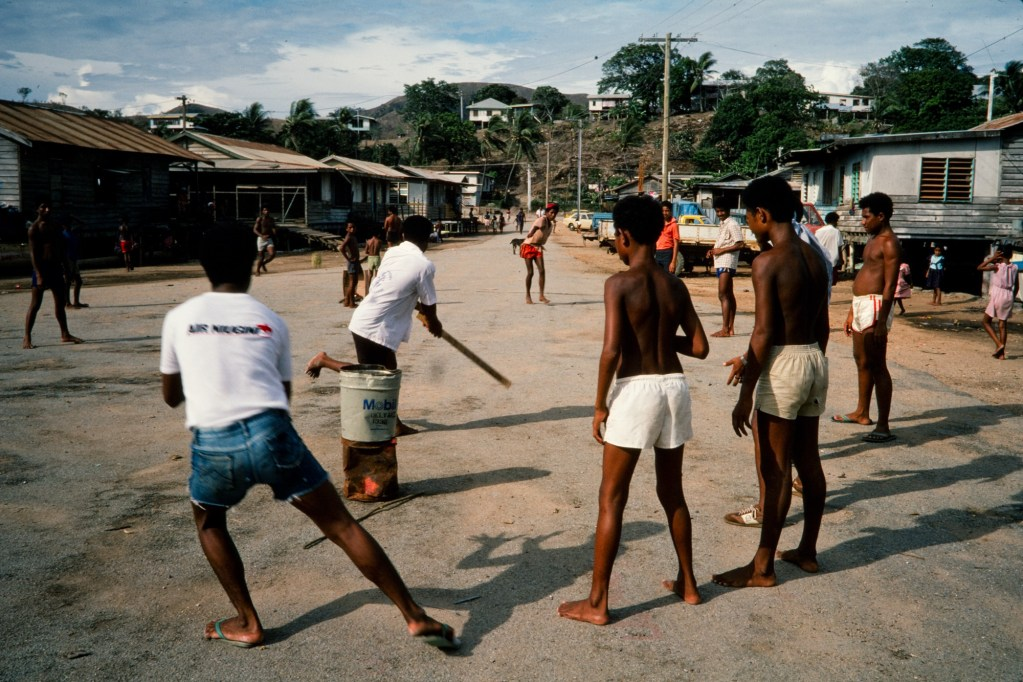 Young Papua New Guinean boys play cricket in the street