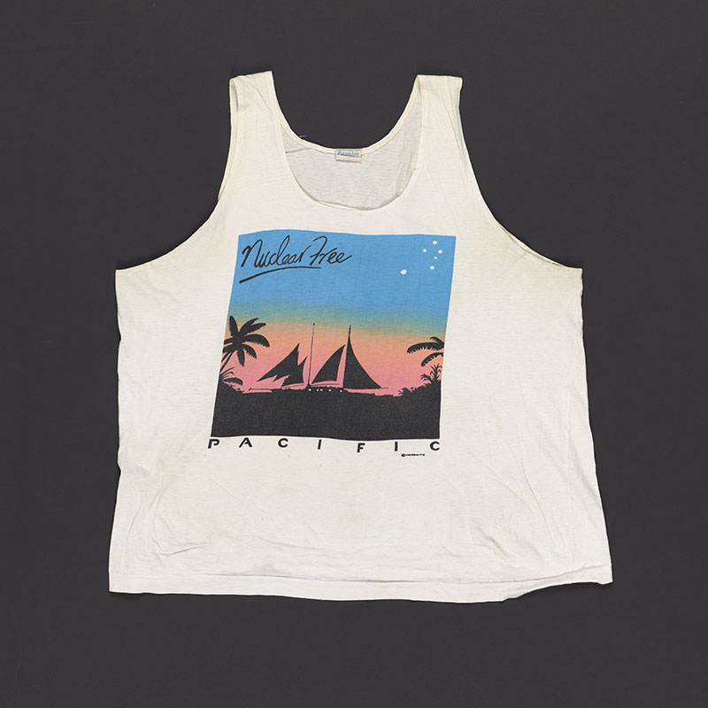 White singlet with a vibrant graphic on it of a silhouetted boat on the ocean surrounded by trees, a pink sky blending into a blue sky, and the words Nuclear free Pacific written on it