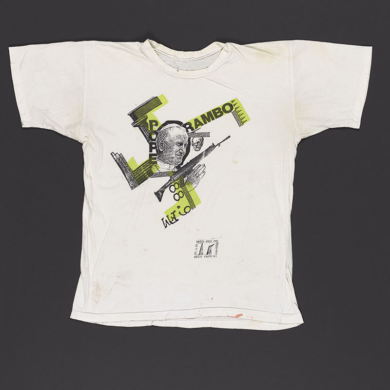 White T-shirt with a picture of Pope John Paul II and the words 'Pope Rambo' and a gun and other graphics shaped like a swastika