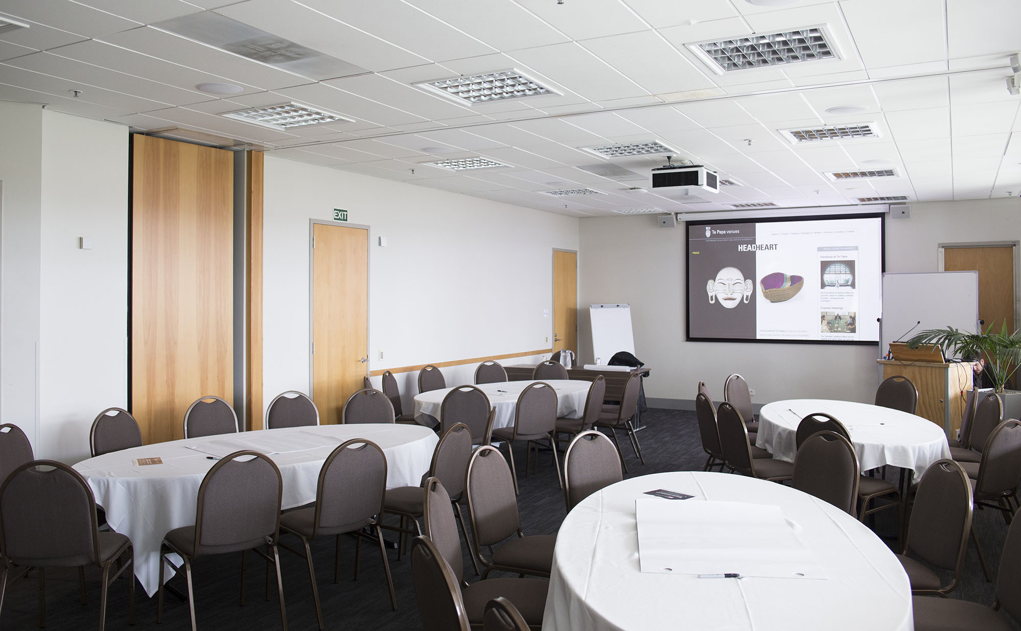Large meeting room with a series of medium-sized tables in it. Each table has a large sheet of paper, and pens. A projector is on the far wall, beside a lantern for a speaker