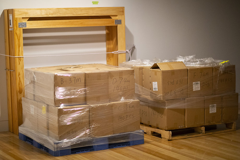 Two large crates of boxes sit on the floor in the gallery