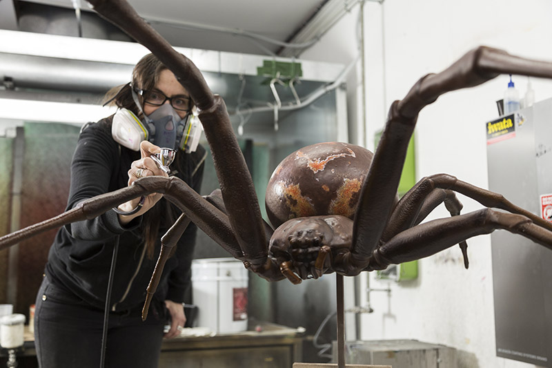 A lady sprays a giant model spider with paint