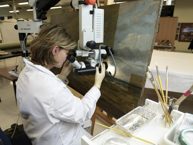 A woman looking at a painting through a piece of scientific equipment