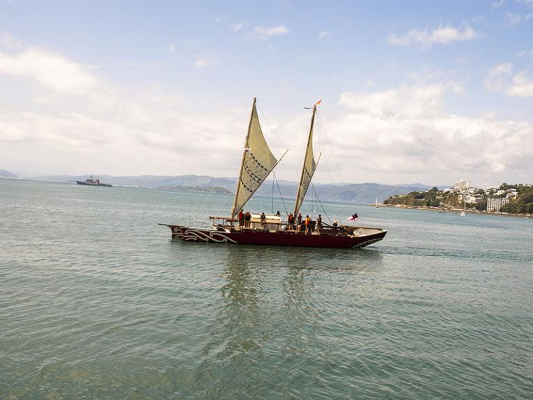 Waka sailing in a harbour on a sunny day