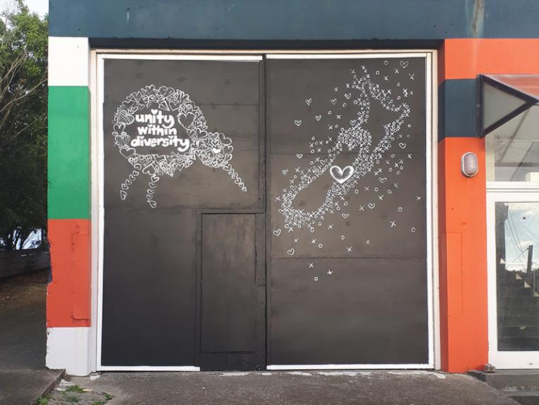 """A black sign on a garage that has a white kiwi and a map of New Zealand drawn on it with the words """"Unity within diversity"""""""