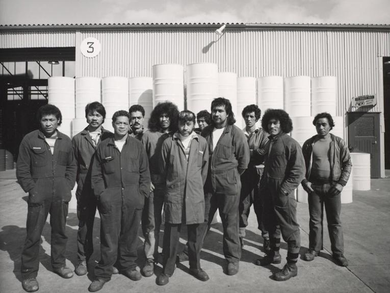 Black and white photo of 11 men in overalls standing in front of a factory