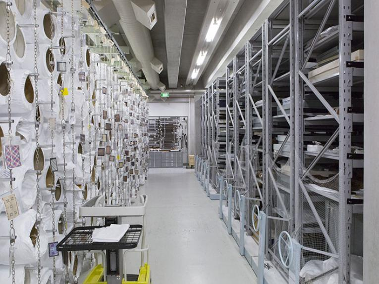 Photo of collection storage area at Te Papa. On the left, is a wall of rolled up tapestries and fabric, on the right are shelves of objects in boxes