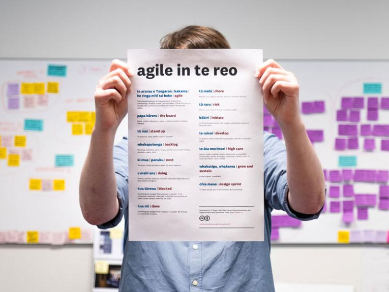 A man holds up a piece of paper with the te reo Māori translations for agile project management words