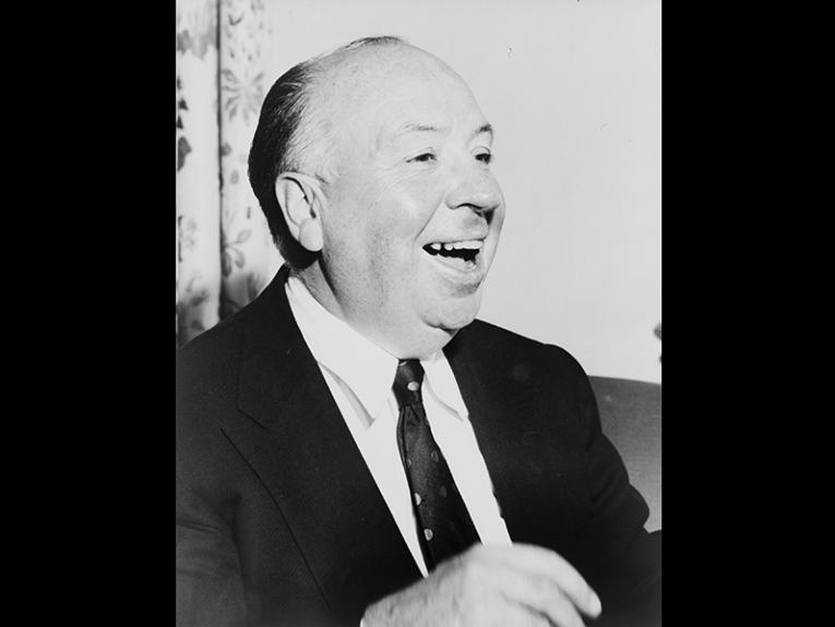 A black and white photo of a bald man laughing
