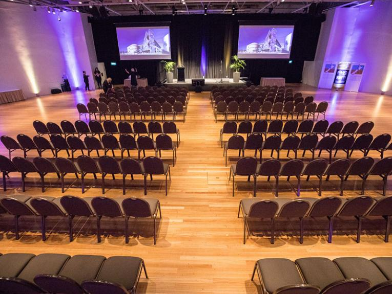Rows of chairs face a stage. On that stage is a lectern, and above it two large projector screens