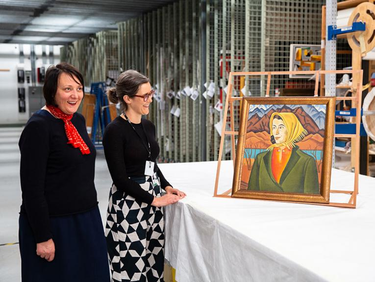 Two women in a painting store room look at a painting on display on a table