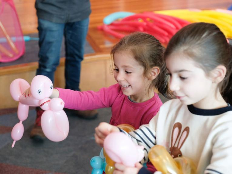 Kids play with animals they've made from balloons