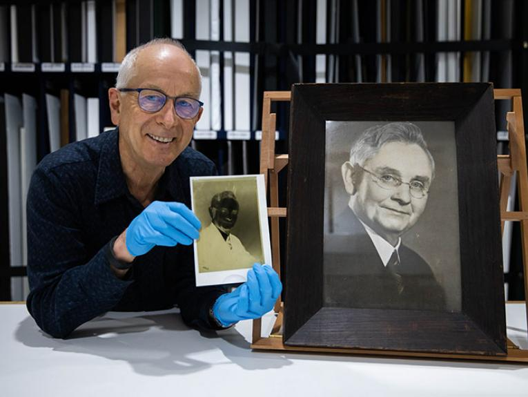 Curator Athol McCredie holds up the negative of the photo of Michael Joseph Savage
