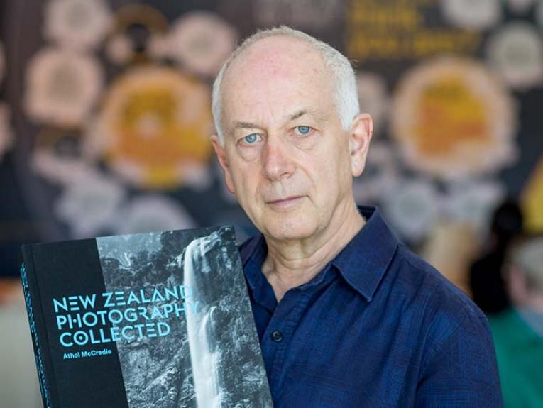 Author Athol McCredie holding copy of his book, New Zealand Photography Collected