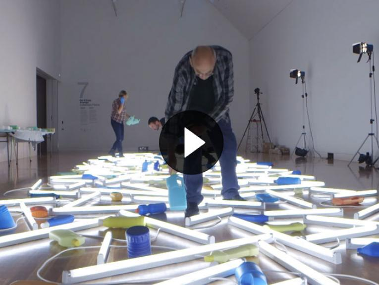 Bill Culbert puts the finishing touches to his art work that involves a number of strip lights and milk bottles on the floor