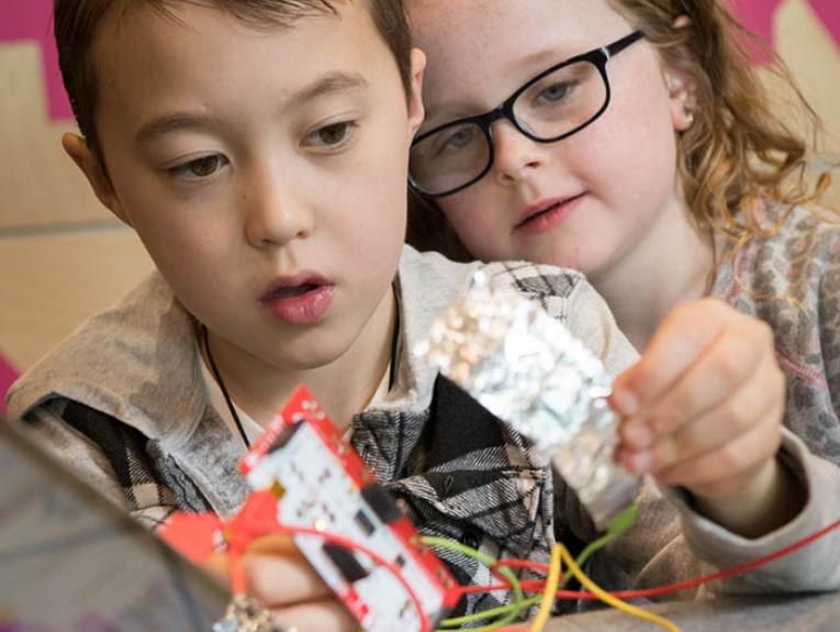 Two children building robots together