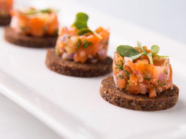 Smoked salmon and macadamia nut tartar on pumpernickel canapé