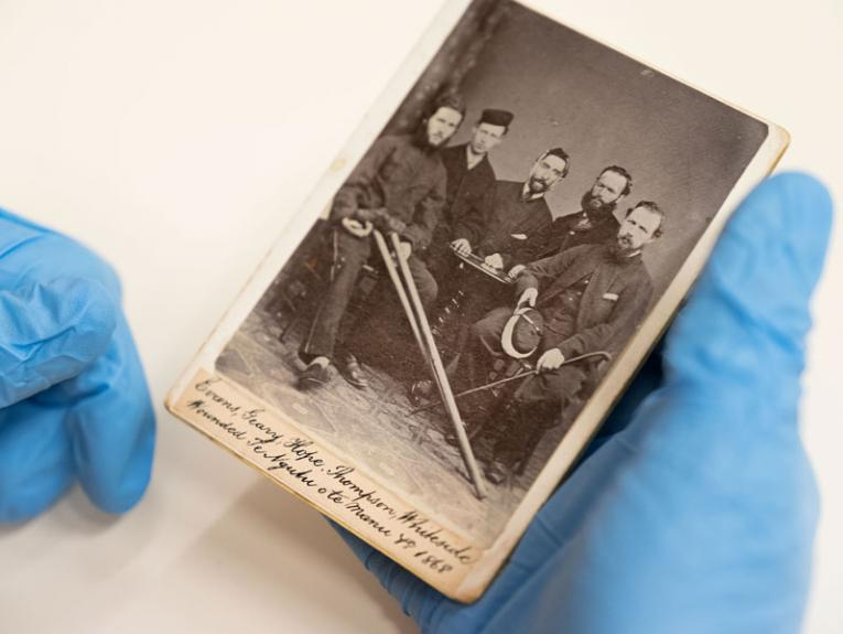 Someone is blue gloves holding an old photograph