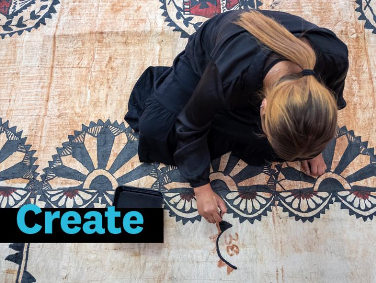 A woman crouching on a tapa cloth painting with black paint