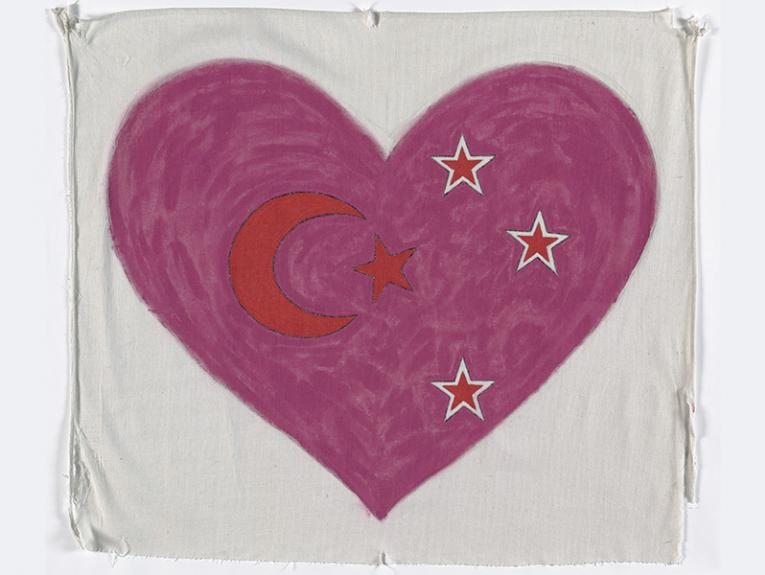 A white piece of cloth with a pink heart painted on it with four stars and a crescent moon in the centre