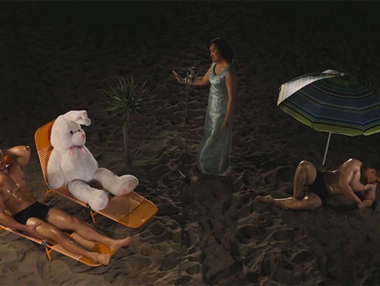 Still from a video, featuring a nightime scene of a sandy area, possibly a beach, with a man and a giant rabbit soft toy sitting in lounge chairs, a lounger singer singing into a microphone, and a man lounging under and umbrella