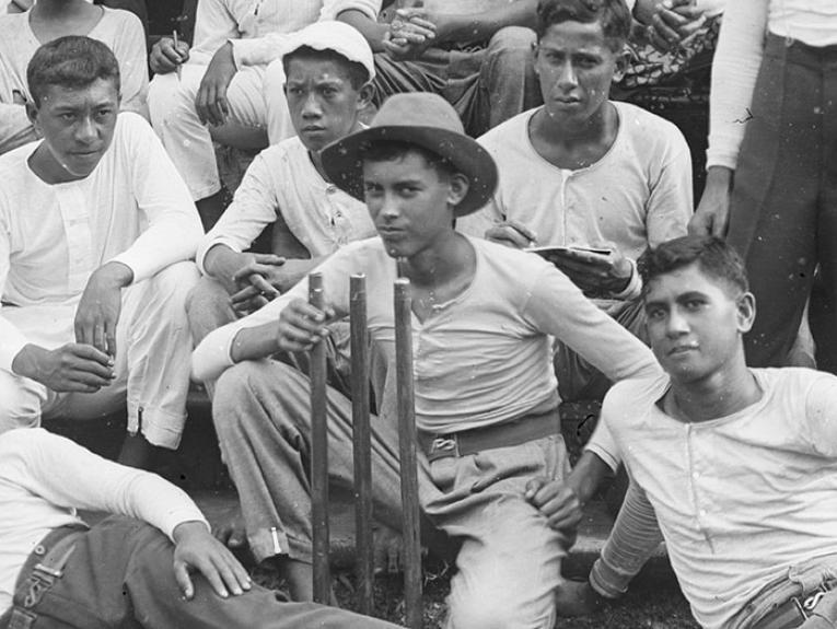 Boys sit holding a cricket wicket